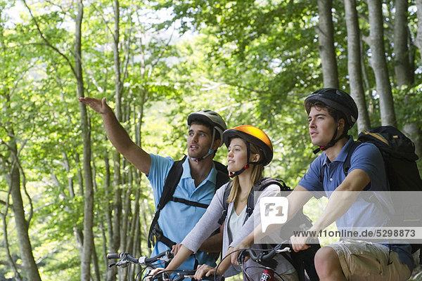 Freunde Fahrrad fahren im Wald  Mann gestikuliert in die Ferne