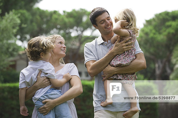 Parents carrying children outdoors