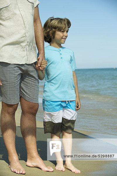 Junge mit Vaters Hand am Strand