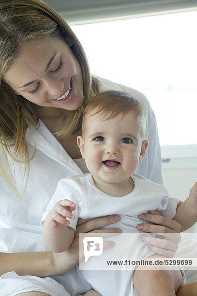 Mutter hält glückliches Baby auf dem Schoß  Portrait