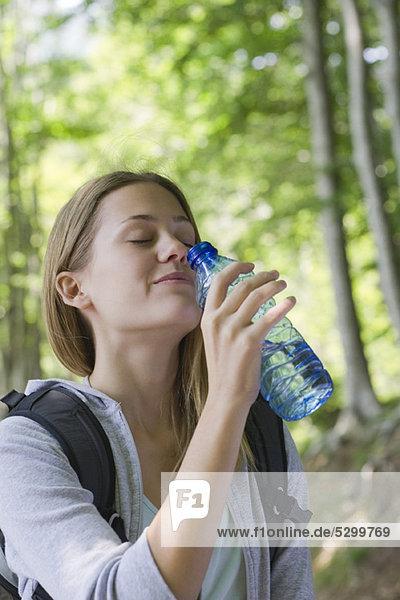 Frau trinkt Flaschenwasser im Wald