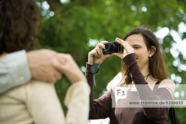 Woman photographing couple with digital camera  over the shoulder view