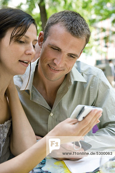 Ein Paar schaut sich das Handy zusammen im Freien an.