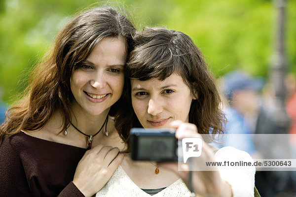 Woman photographing herself with friend