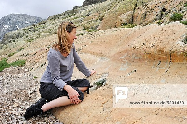 young woman watching the petroglyph named Le Sorcier Vallee des Merveilles  Mercantour National Park Alpes-Maritimes department  Provence-Alpes-Cote d´Azur region  southeast of France  Europe