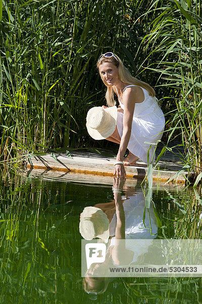 Frau hockt auf einem Holzsteg am Wasser