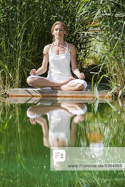 Frau macht eine Yogaübung am Wasser