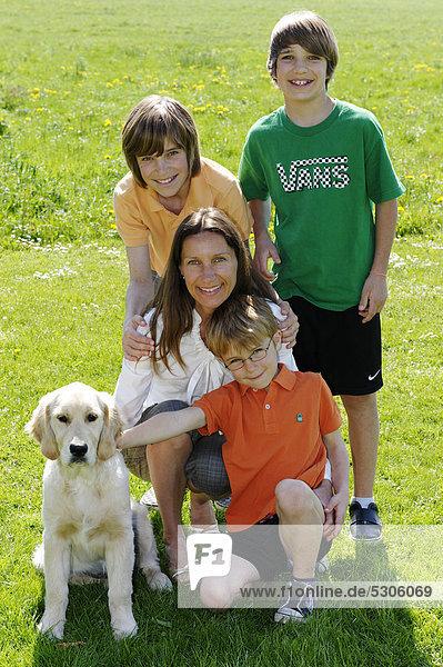 Mutter mit ihren drei Söhnen und Hund
