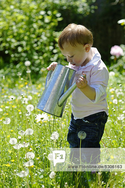 Kleiner Junge  2 Jahre  spielt mit einer Gießkanne im Garten