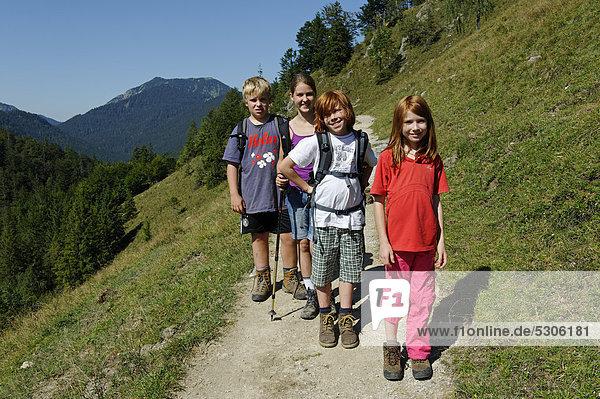 Children hiking to Koenigsalm mountain pasture  Weissachtal valley  Tegernsee area  Blauberge mountain range  Upper Bavaria  Bavaria  Germany  Europe