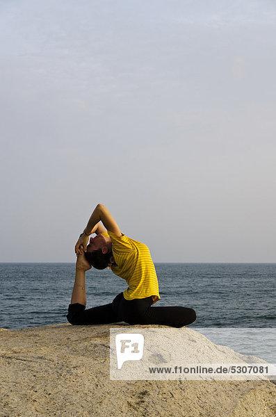 Frau in Yoga-Position Kapotasana  am Meer in Kanyakumari  Tamil Nadu  Indien  Asien