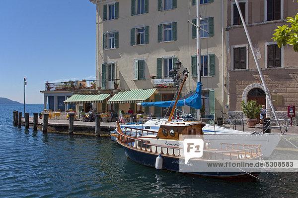 Restaurant und Boote im Hafen von Gargnano  Gardasee  Provinz Brescia  Lombardei  Italien  Europa