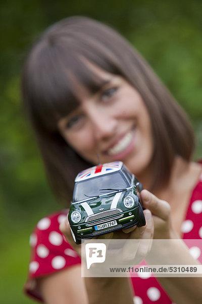 Junge Frau  25 Jahre  zeigt ein Modellauto
