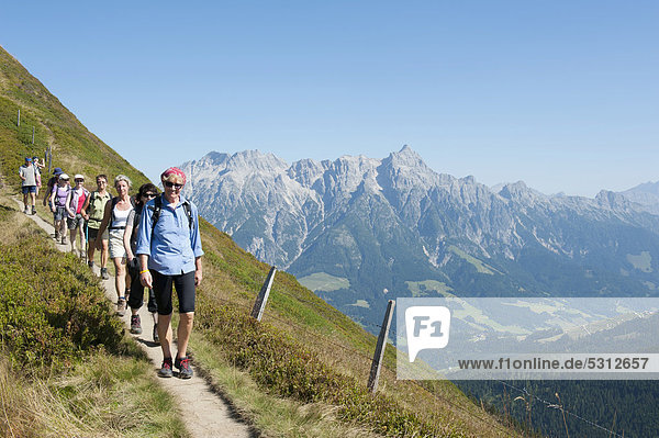 Hiking group walking along a narrow path  Northern Limestone Alps  in front of Leogang Stone Mountains  the Alps  Saalbach-Hinterglemm  Salzburg  Austria  Europe