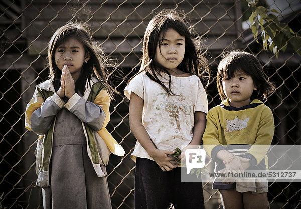 Drei traurige Mädchen vor Zaun in Laos  Südostasien  Asien