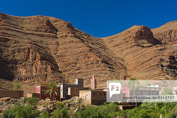 Small village with a mosque in front of red rock walls  Ait Mansour Valley  Anti-Atlas Mountains  southern Morocco  Morocco  Africa