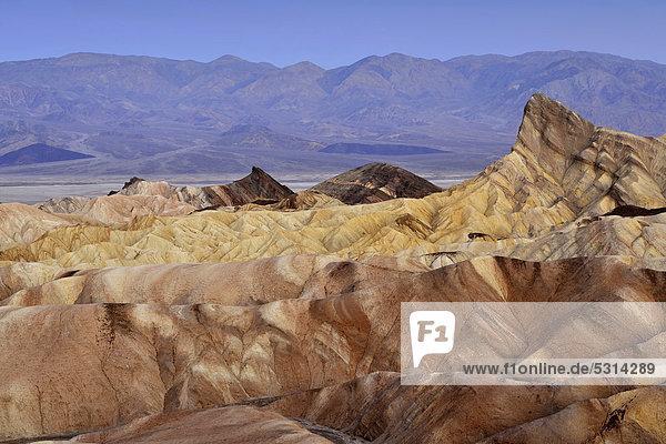 Blick von Zabriskie Point auf durch Mineralien verfärbtes erodiertes Gestein des Manly Beacon  dahinter Panamint Range  Morgendämmerung  Death Valley Nationalpark  Mojave-Wüste  Kalifornien  Vereinigte Staaten von Amerika  USA