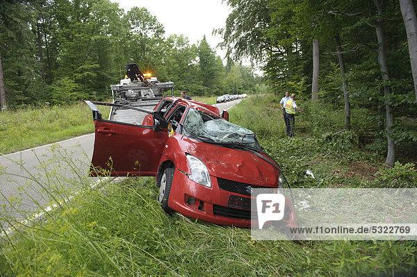 Ein roter Suzuki Swift liegt nach einem Verkehrsunfall auf der K 1209 beschädigt auf dem Dach  Lichtenwald  Baden-Württemberg  Deutschland  Europa
