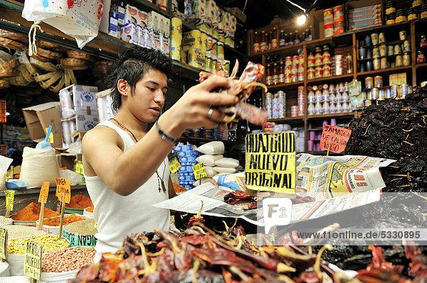 Jugendlicher verkauft in seinem Marktstand offene Gewürze und andere Lebensmittel  Abpacken von Chili-Schoten  städtischer Markt von Puebla  Mexiko  Mittelamerika
