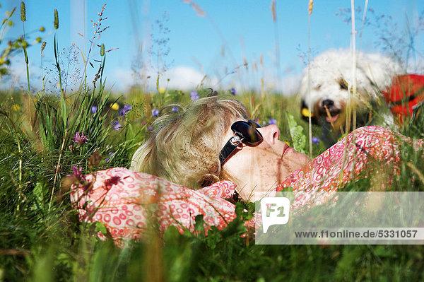 Frau mit Hund liegt auf einer Wiese  Schwarzwald  Baden-Württemberg  Deutschland  Europa Frau mit Hund liegt auf einer Wiese, Schwarzwald, Baden-Württemberg, Deutschland, Europa