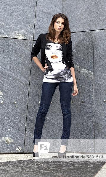 Junge Frau in Top mit Porträtmotiv und Jeans posiert an grauer Wand
