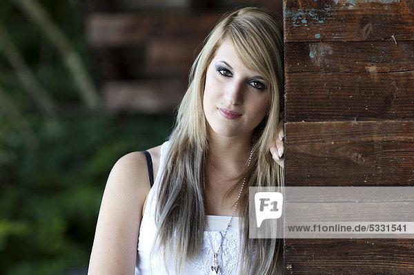 Junge Frau mit langen blonden Haaren posiert stehend an Holzwand  Portrait