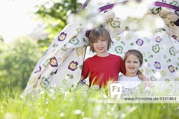 Kinder spielen im Park in einem Zelt