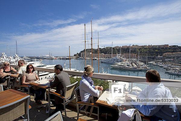 People sitting in a restaurant on the Quai des Etats quay  harbour  Monte Carlo  Principality of Monaco  Europe