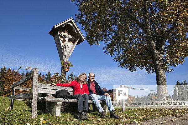 Paar  45 und 55 Jahre  auf Bank unter Kruzifix im Herbst  Alpenvorland  Oberbayern  Bayern  Deutschland  Europa Paar, 45 und 55 Jahre, auf Bank unter Kruzifix im Herbst, Alpenvorland, Oberbayern, Bayern, Deutschland, Europa