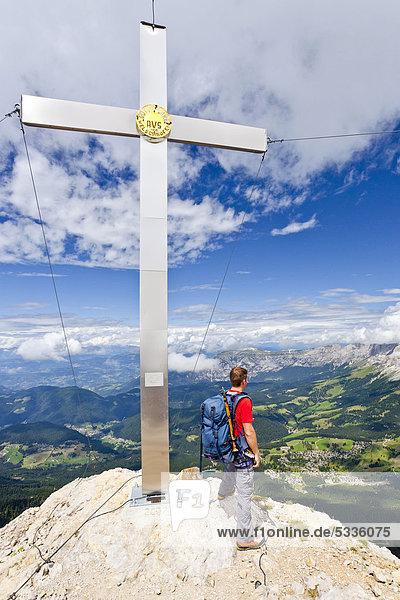 Bergsteiger am Gipfelkreuz bei der Latemarüberschreitung  Latemarspitz  hinten die Rosengartengruppe  Dolomiten  Südtirol  Italien  Europa Bergsteiger am Gipfelkreuz bei der Latemarüberschreitung, Latemarspitz, hinten die Rosengartengruppe, Dolomiten, Südtirol, Italien, Europa