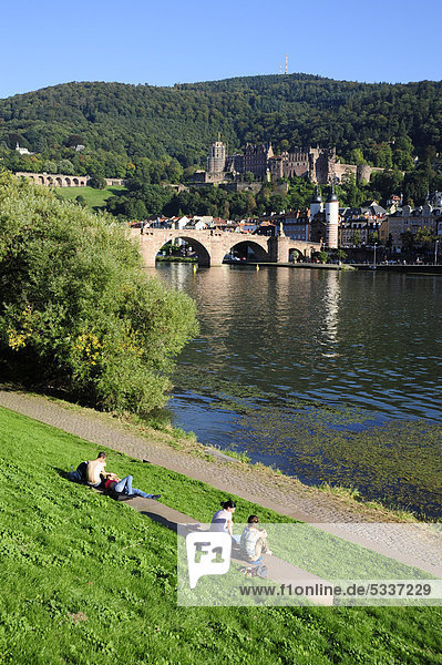People at the Neckar river  at back the Alte Bruecke or Karl-Theodor-Bruecke bridge and the historic district of Heidelberg  Neckar valley  Baden-Wuerttemberg  Germany  Europe