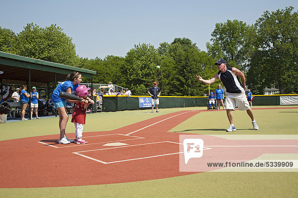 Child with disabilities plays baseball in the Miracle League  supported by a buddy who volunteers to help the child  Southfield  Michigan  USA