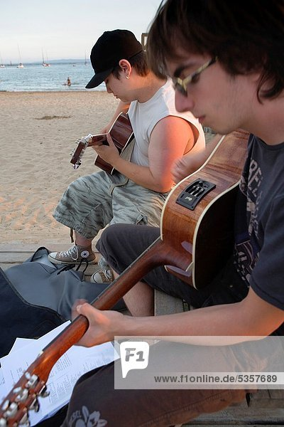 Roses Two friends Playing the guitar in Gran beach Costa Brava Girona province Catalonia Spain