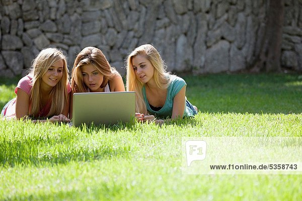 Group of Teenagers with laptop in the garden