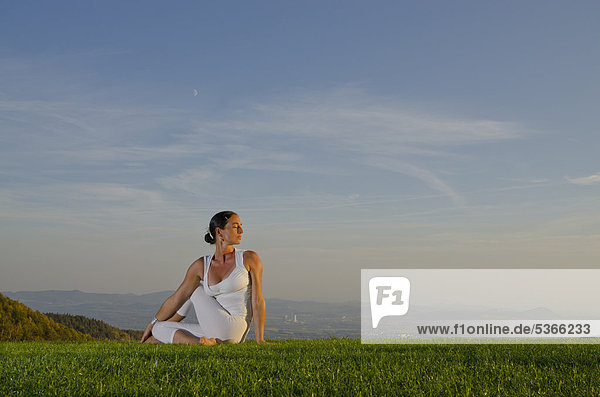 Junge Frau praktiziert Hatha-Yoga im Freien  zeigt die Stellung ardha matsyendrasana  halber Drehsitz  Nove Mesto  Okres Teplice  Tschechische Republik  Europa