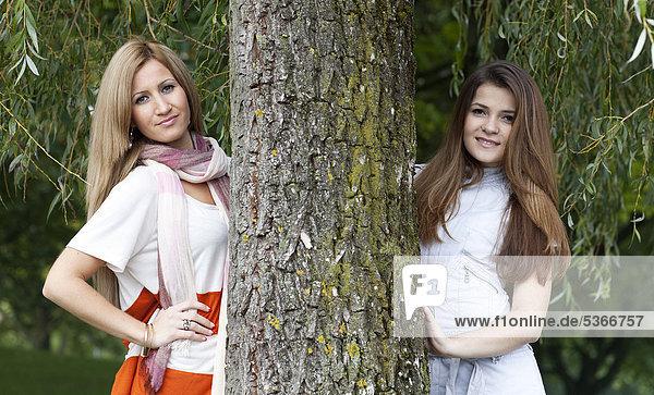 Zwei junge Frauen neben einem Baumstamm