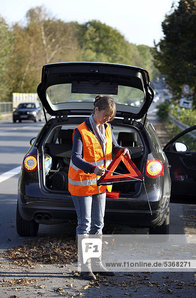 Autopanne  Fahrerin hat auf dem Seitenstreifen einer Landstraße angehalten  trägt eine Warnweste  stellt ein Warndreieck auf