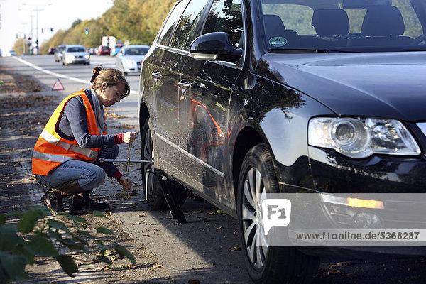 Autopanne  Fahrerin hat auf dem Seitenstreifen einer Landstraße angehalten  trägt eine Warnweste  wechselt ein defektes Rad aus