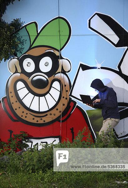 Mann surft mit Laptop vor Graffitiwand  Symbolbild Computerhacker  Computerkriminalität  Internetkriminalität  Datenklau