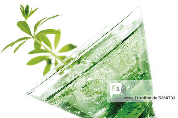 Glass of sweet woodruff punch with ice cubes