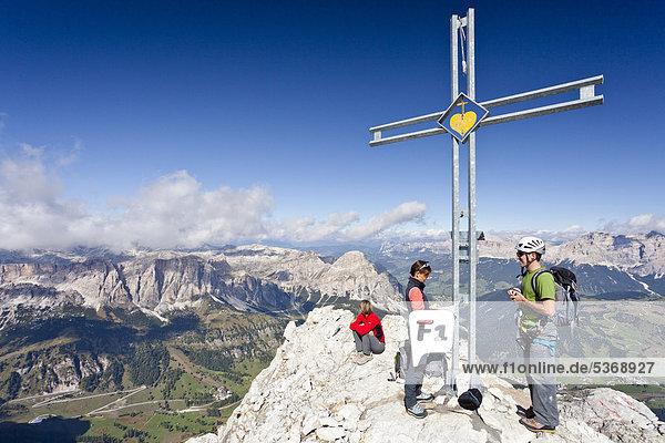 Bergsteiger am Gipfelkreuz Boeseekofel  hinten Fanesgruppe und Heiligkreuzkofelgruppe  Dolomiten  Südtirol  Italien  Europa Bergsteiger am Gipfelkreuz Boeseekofel, hinten Fanesgruppe und Heiligkreuzkofelgruppe, Dolomiten, Südtirol, Italien, Europa