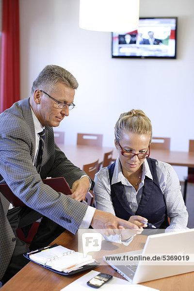 Mann  54 Jahre  und Frau  40 Jahre  beim Geschäftsgespräch