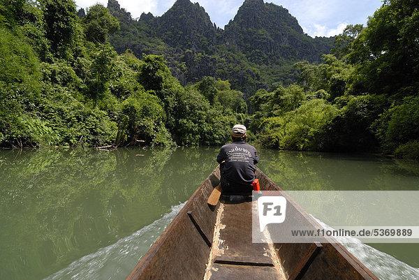 Laotischer Bootsmann mit einfachem Langboot vor dem Eingang der 7  5 km langen Höhle Tham Konglor  Tham Kong Lor  im dichten subtropischen Regenwald  Khammouane  Laos  Südostasien  Asien