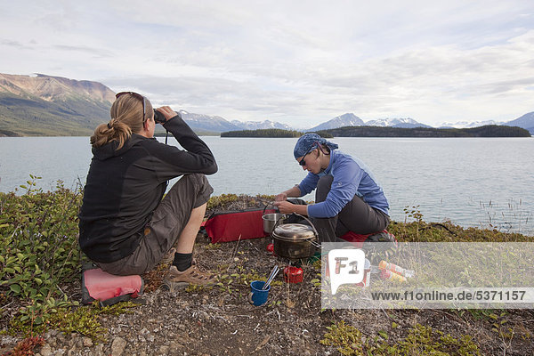 Two young women cooking on a camping stove  watching lake with binoculars  Atlin Lake  British Columbia  Canada  America