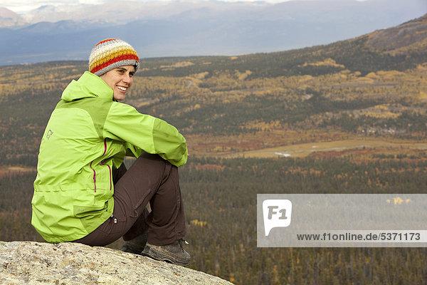 Junge Frau sitzt auf einem Felsen auf einem Berg  rastet  genießt Aussicht  subalpine Tundra  Indian Summer  Herbst  in der Nähe des Fish Lake  Yukon Territory  Kanada