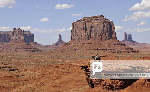 Aussichtspunkt John Ford's Point  Touristin auf Pferd  Tafelberge East Mitten Butte  West Mitten Butte  Merrick Butte  Castle Butte  Bear and Rabbit  Stagecoach  Mitchell Mesa  Monument Valley  Navajo Tribal Park  Navajo Nation Reservation  Arizona  Utah  Vereinigte Staaten von Amerika  USA