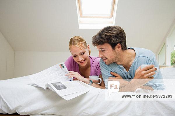 Junges Paar lesen Magazin im Bett