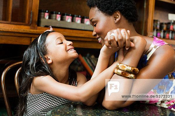 Mutter und Tochter Hand in Hand im cafe