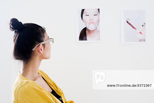 Junge Frau Modedesigner betrachten Fotos auf weiße Wand