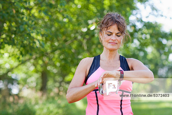 Frau kontrolliert die Uhr während des Trainings